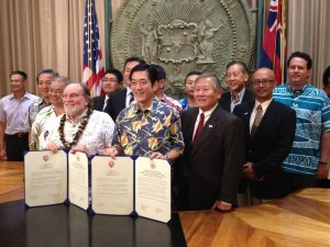Govs. Abercrombie and Nakamura flanked by Rep. Ken Ito, Sen. Will Espero and DBEDT Director Richard Lim show off the reaffirmation documents.