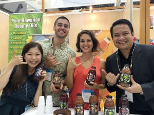 Shaka Tea owners Harrison Rice and Bella Hat the Tokyo Gift Show with DBEDT director Luis Salaveria and their translator